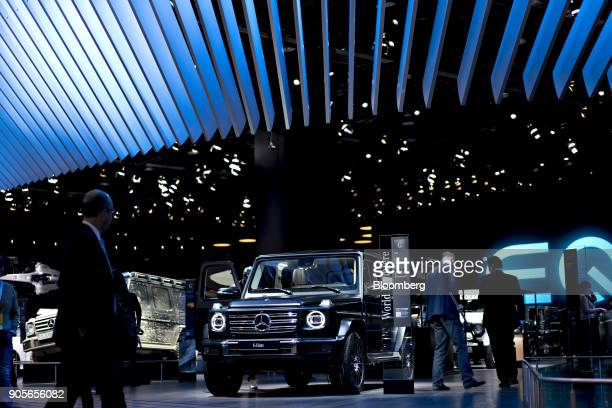 Attendees walk past the Daimler AG MercedesBenz G 500 vehicle during the 2018 North American International Auto Show in Detroit Michigan US on...