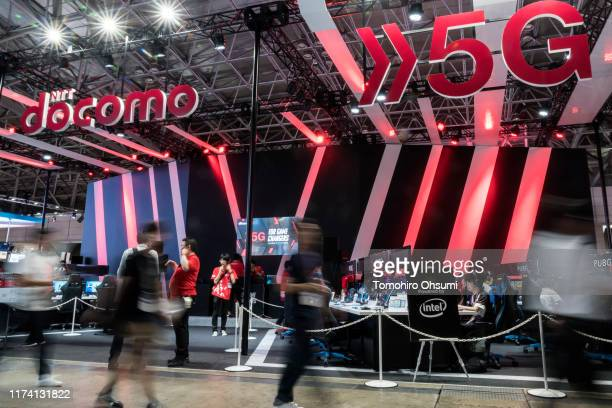 Attendees walk past the NTT Docomo Inc. Booth promoting the 5G networks on the business day of the Tokyo Game Show 2019 at Makuhari Messe on...