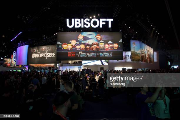 Attendees walk past the Ubisoft Entertainment SA booth during the E3 Electronic Entertainment Expo in Los Angeles California US on Wednesday June 14...