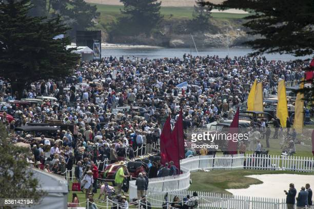 Attendees walk the grounds during the 2017 Pebble Beach Concours d'Elegance in Pebble Beach California US on Sunday Aug 20 2017 Official estimates...