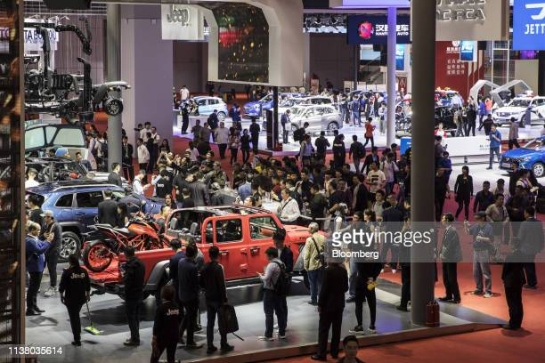 Attendees walk through Fiat Chrysler Automobiles NV's Jeep booth at the Auto Shanghai 2019 show in Shanghai, China, on Thursday, April 18, 2019....