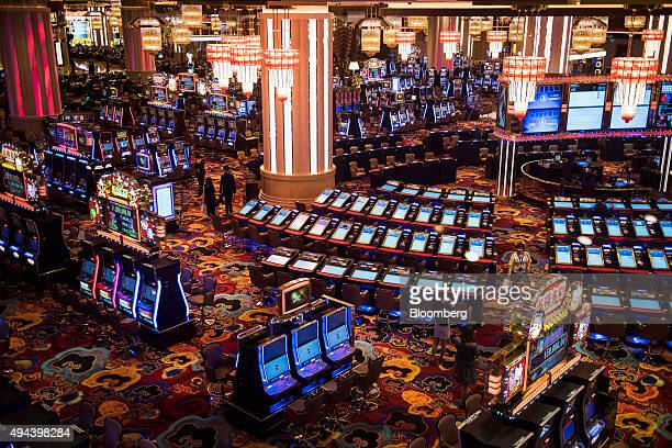 Attendees walk through the gaming floor of the casino at the Studio City casino resort developed by Melco Crown Entertainment Ltd ahead of the grand...