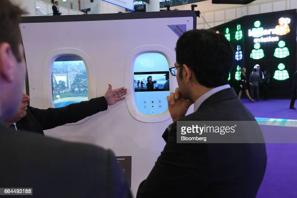 Attendees watch a demonstration of a smart interactive window technology manufactured by Acti-Vision at the Aircraft Interiors Expo in Hamburg,...