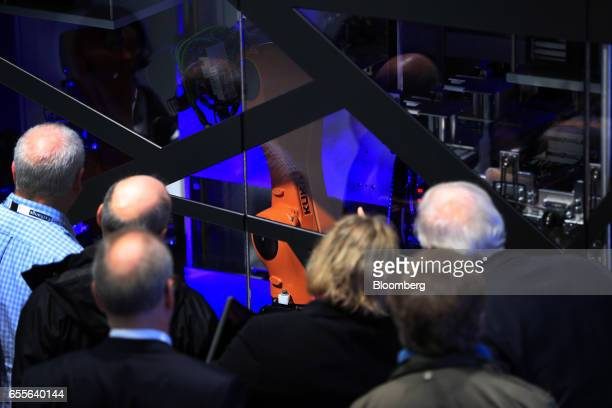Attendees watch a Kuka AG robotic arm operate behind a screen at the CeBIT 2017 tech fair in Hannover Germany on Monday March 20 2017 Leading edge...