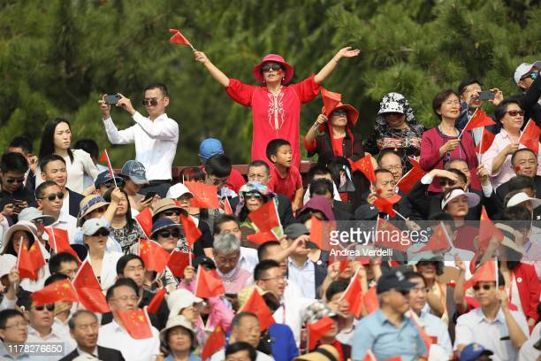 Attendees watch a military parade and wave the flag of China during a parade to celebrate the 70th Anniversary of the founding of the People's...