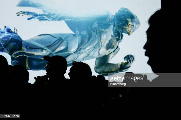 Attendees watch a preview for the Anthem video game during an Electronic Arts Inc Play event ahead of the E3 Electronic Entertainment Expo in Los...