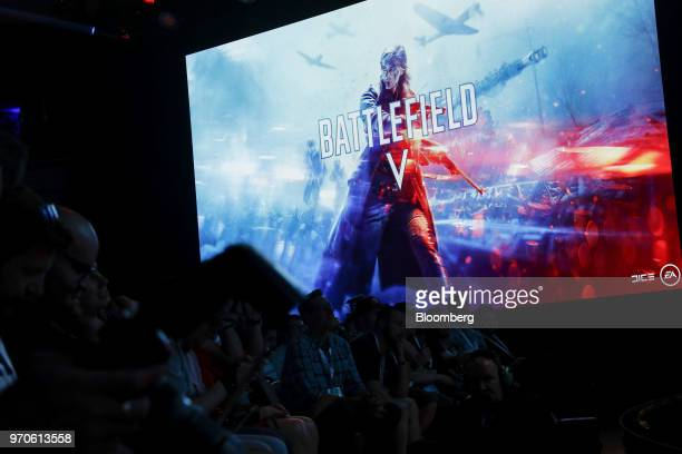 Attendees watch a preview for the Battlefield V video game during an Electronic Arts Inc Play event ahead of the E3 Electronic Entertainment Expo in...