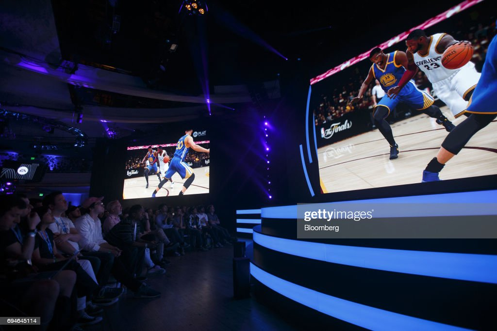 Attendees watch a preview of 'NBA Live 18' during the Electronic Arts Inc. (EA) Play event ahead of the E3 Electronic Entertainment Expo in Los Angeles, California, U.S., on Saturday, June 10, 2017. EA revealed two new titles along with the annual iterations of the company's sports games, as well as unveiling the highly anticipated 'Star Wars: Battlefront II' open-world multiplayer gameplay. Photographer: Patrick T. Fallon/Bloomberg via Getty Images
