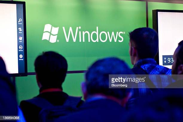 Attendees watch a product demonstration near a Windows logo in the Microsoft Corp booth at the 2012 International Consumer Electronics Show in Las...