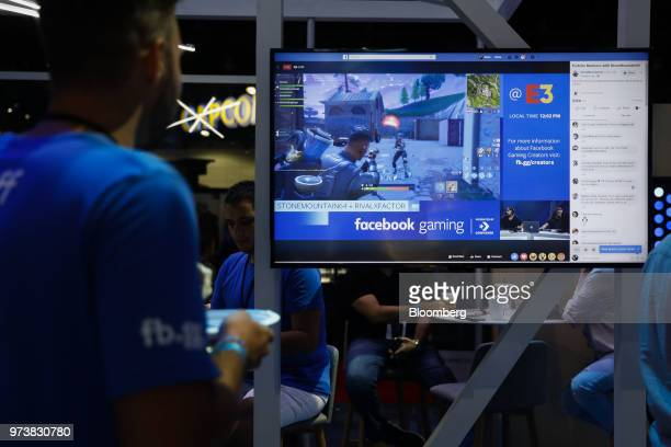 Attendees watch a stream of the Epic Games Inc Fortnite Battle Royale video game at the Facebook Inc gaming booth during the E3 Electronic...