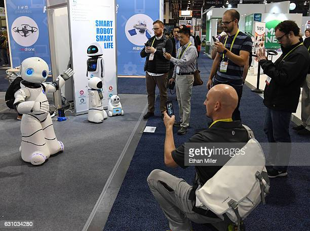 Attendees watch a Tanscorp UU smart robot dance to a Michael Jackson song it is playing at CES 2017 at the Sands Expo and Convention Center on...