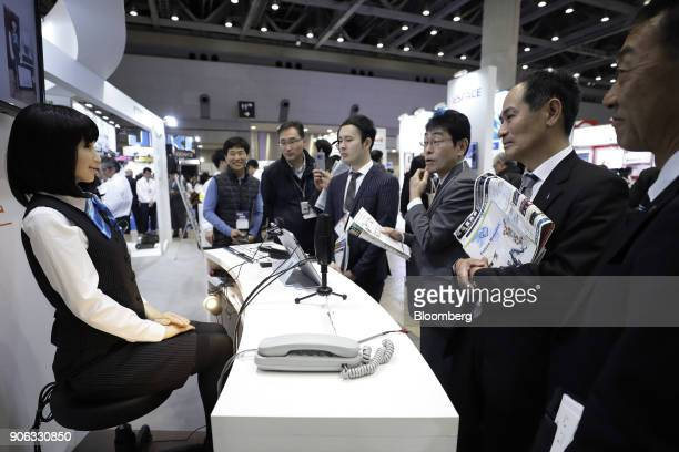 Attendees watch as a Kokoro Co Actroid humanoid robot using Kyoei Sangyo Co's 'RecepROID' software performs during a demonstration at the RoboDEX...