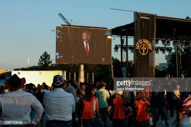 """Attendees watch as a video message from former U.S. President Donald Trump plays during a """"Let Us Worship"""" prayer service on the National Mall on..."""