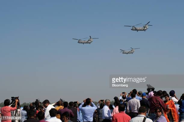 Attendees watch Indian Air Force Boeing CH-47 Chinook helicopters fly by during the Air Force Day Parade at Air Force Station Hindan in Ghaziabad,...