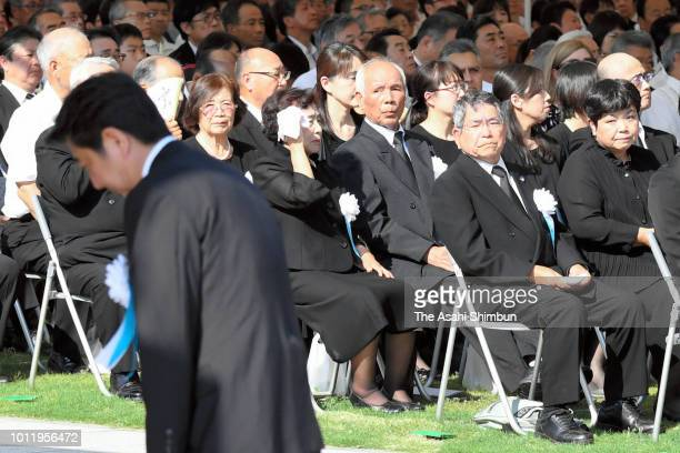 Attendees watch Prime Minister Shinzo Abe after his address during the Peace Memorial Ceremony at Hiroshima Peace Memorial Park on the 73rd...