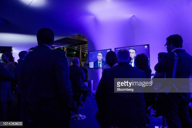 Attendees watch television screens showing Jair Bolsonaro presidential candidate for the Social Liberal Party speaking during the first presidential...