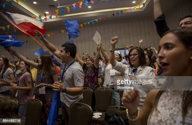 Attendees wave a Chilean national flag and cheer as they react to exit poll results at the National Renewal party headquarters after the second round...
