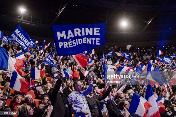 Attendees wave flags and hold signs during a presidential campaign event in Lyon France on Sunday Feb 5 2017A BVA poll says France's National Front...