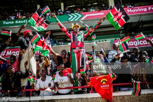 Attendees wave Kenyan flags during the independence celebrations on Jamhuri Day at Kasarani stadium in Nairobi Kenya on Tuesday Dec 12 2017 Kenyas...