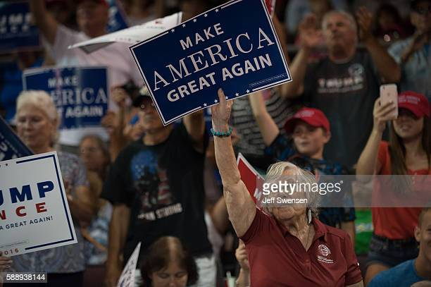 Attendees wave signs for Republican candidate for President Donald Trump as he speaks at a rally at Erie Insurance Arena on August 12, 2016 in Erie,...
