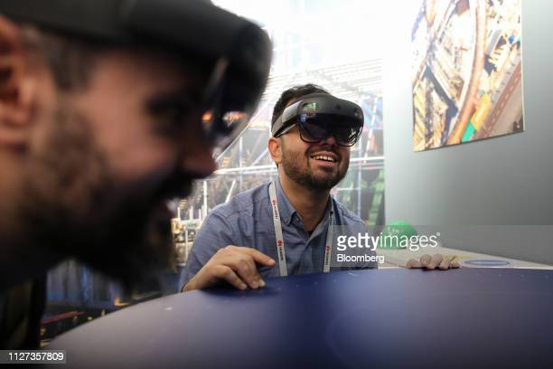 Attendees wear Microsoft Corp HoloLens 2 headsets as they use the Bentley Systems Inc Synchro XR augmented reality app at the Microsoft Corp stand on...