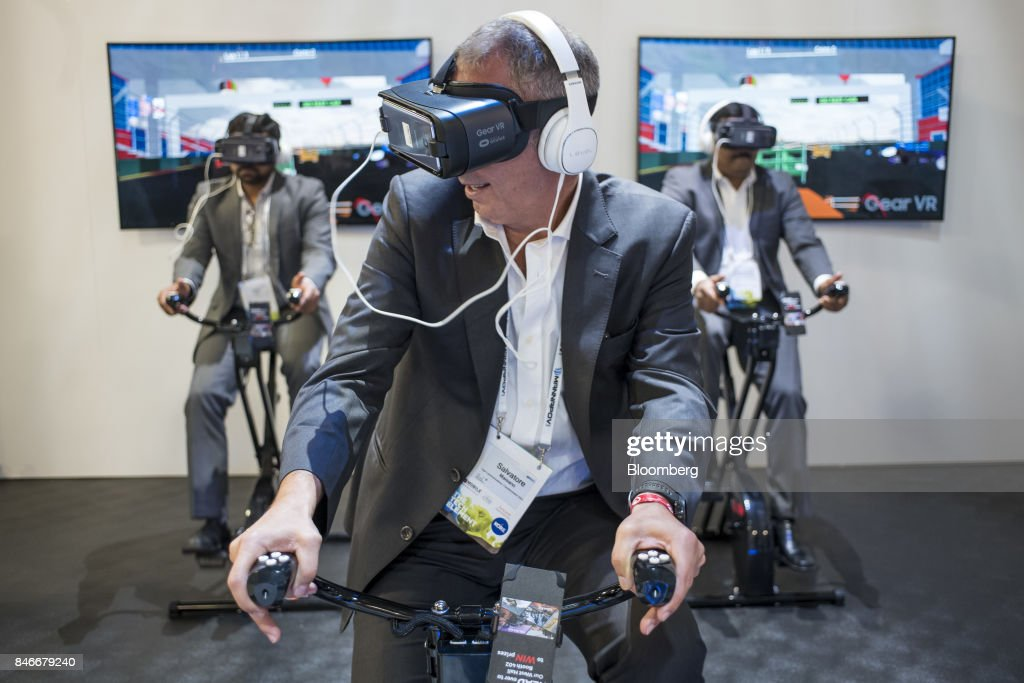 Attendees wear Samsung Electronics Co. Galaxy Gear Virtual Reality (VR) headsets with Galaxy S8 smartphones and Level On headphones as they try the VirZOOM Inc. fitness workout on VZ Bike Controllers during the Mobile World Conference Americas event in San Francisco, California, U.S., on Wednesday, Sept. 13, 2017. Leaders from the mobile ecosystem will be presenting the challenges and opportunities in the industry and the impact it has on society. Photographer: David Paul Morris/Bloomberg via Getty Images