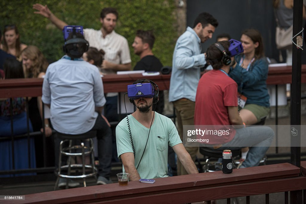Attendees wear virtual reality headsets while attending a private party during the South By Southwest (SXSW) Interactive Festival at the Austin Convention Center in Austin, Texas, U.S., on Monday, March 14, 2016. The SXSW Interactive Festival features presentations and panels from the brightest minds in emerging technology, scores of networking events hosted by industry leaders and a lineup of special programs showcasing new websites, video games, and startup ideas. Photographer: David Paul Morris/Bloomberg via Getty Images