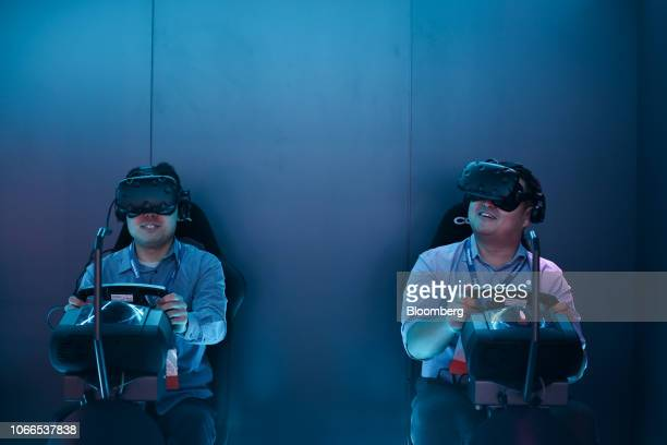 Attendees wear virtual reality headsets while participating in the Jaguar Land Rover Automotive Plc virtual drive experience during AutoMobility LA...