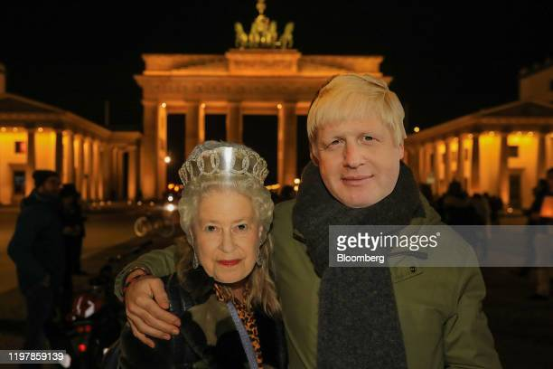 Attendees wearing face masks depicting Britain's Queen Elizabeth II and UK Prime Minister Boris Johnson embrace during a flashmob gathering at...