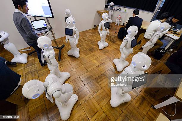 Attendees work with humanoid robots named Pepper developed by SoftBank Corp's Aldebaran Robotics unit during a Softbank developer's workshop for...