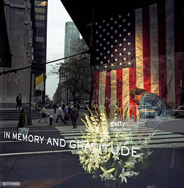 Attending to a floral memorial of Lillies in a 5th Avenue store front in midtown Manhattan In the days following the September 11th attacks a store...