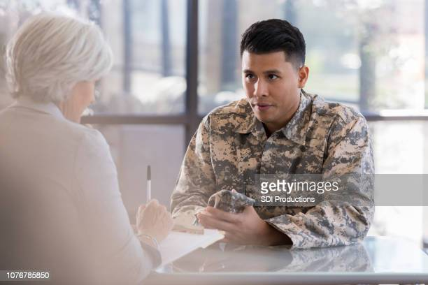 attentive army soldier listens to therapist - military doctor stock photos and pictures