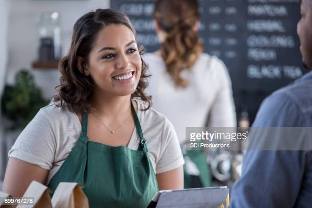 Attentive barista talks with customer