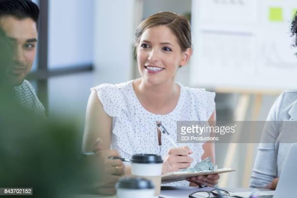 Femme d'affaires attentionné prend des notes au cours de la réunion