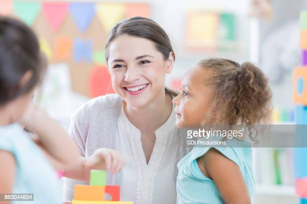 Attentive child care worker sits with children after school