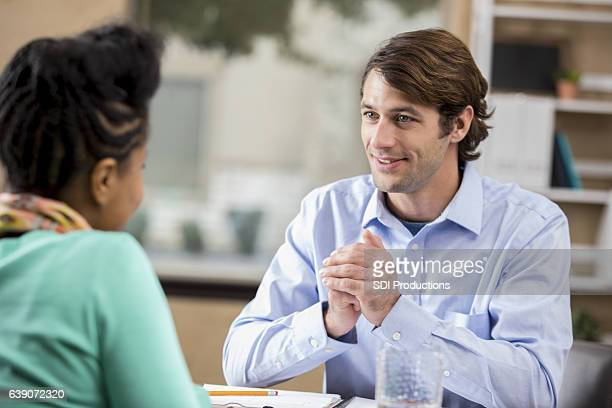 Attentive counselor listens to African American female patient