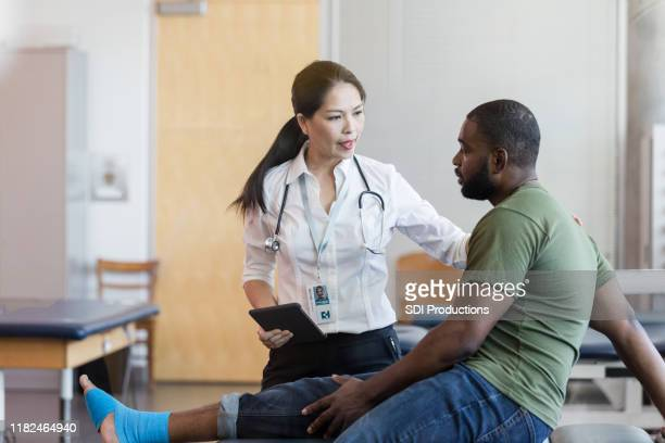 attentive doctor listens to injured male soldier - army physical exam stock pictures, royalty-free photos & images