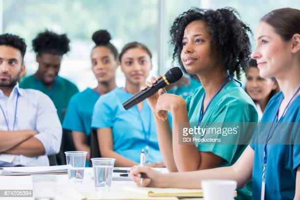 Attentive female physician answers question during panel discussion