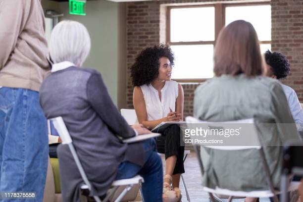 attentive homeowner association president meets with neighbors - organised group stock pictures, royalty-free photos & images