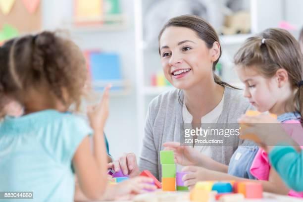 attento insegnante d'asilo si siede con gli studenti - servizi per l'infanzia foto e immagini stock