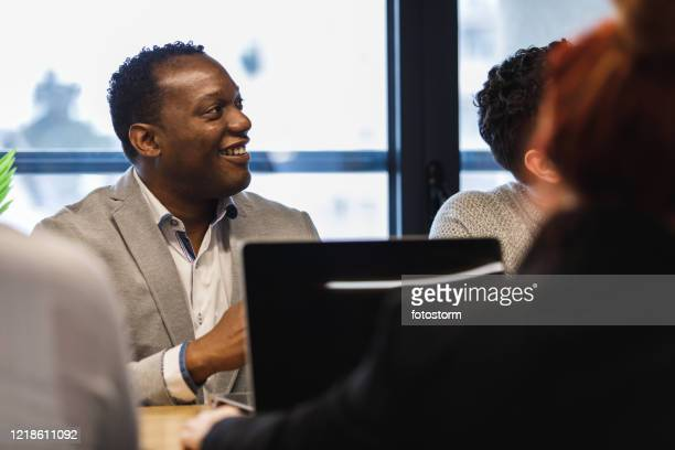 attentive looks on the team meeting in shared office space - hub stock pictures, royalty-free photos & images