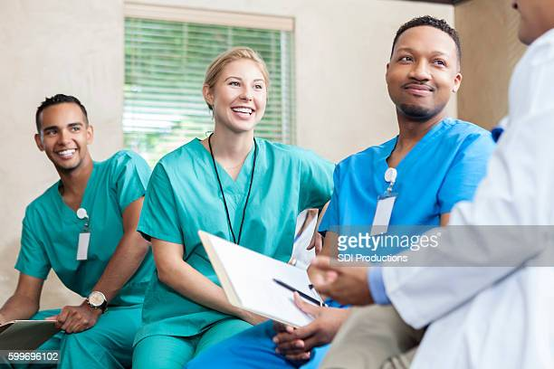 Attentive medical staff talk with colleague