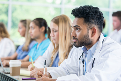 Attentive medical student takes notes during class 872085204