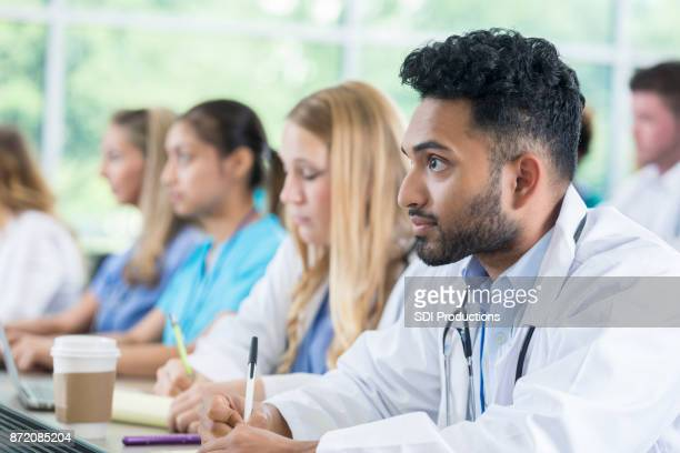 Attentive medical student takes notes during class