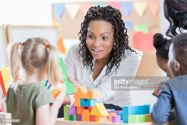 Attentive preschool teacher reads story book to school children