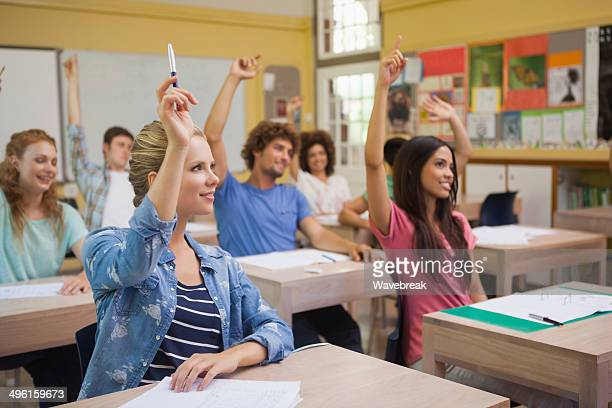 Attentive students raising hands in classroom