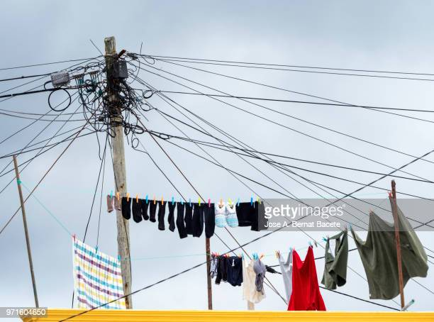 Attic of a house with a rope with stretched clothes line on a pole of electricity and telephone against sky on Terceira Island in the Azores Islands, Portugal.