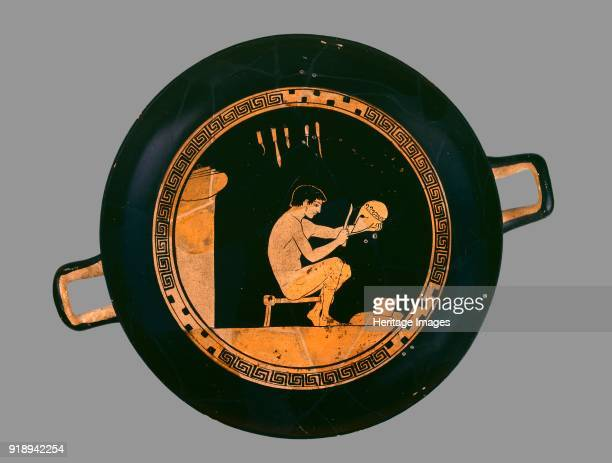 Attic redfigure cup depiting a seated helmet maker and his equipment c480 BC Athenian redfigure cup depiction of a helmet maker and his equipment the...