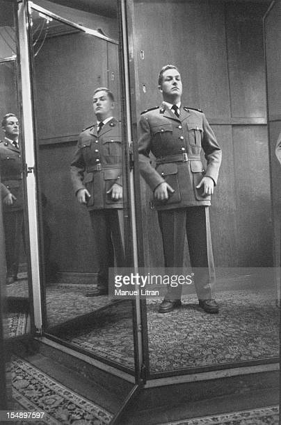 Attitude of JeanMarie Le Pen trying his uniform to a tailor in PARIS looking in a mirror his reflected image several times