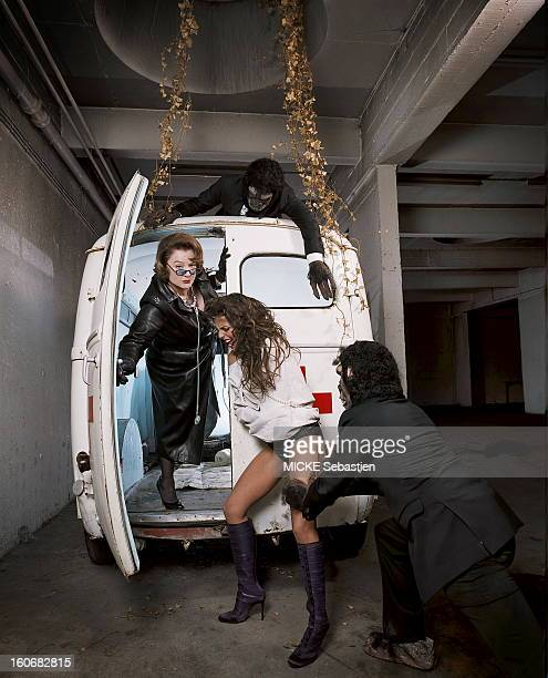 Attitude of Josiane Balasko clothed all in black leather opened the back door of an old ambulance to make up a young woman pushed by a man dressed as...